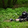 Boy paintball player lies with gun in ambush on grass near fence — Vídeo Stock