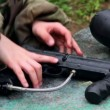 Hands take paintball gun and put it back under rain — Stock Video