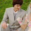 Stock Video: Newly-married couple sitting on meadow are fastened to handcuffs