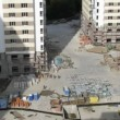 Stock Video: Workers walk on building site in housing estate below