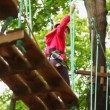 Stock Video: Girl goes on boards suspended in wood, strong keeping for ropes