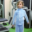 Stock Video: Little girl exercises with dumbbells at background of training equipment near mirror