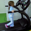 Stock Video: Little girl walks by treadmill and looks to panel with hands on handholds