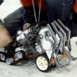 Stock Video: People operate with toy robot on floor