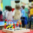 Stock Video: Conundrum toy standing on table, in defocus behind it children play