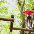 Girl crosses on linked logs and suspended on height in wood — Stock Video