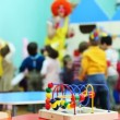 Stock Video: Conundrum toy standing on table, in defocus clown blow bubbles for children
