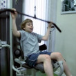 Little boy sits and hauls light weight on training equipment — Vídeo de stock