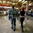 Stock Video: Man in futuristic suit and girl with guns walk in exhibition hall during Game Developers Conference 2011