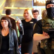 Man in special force uniform stand among people during Game Developers Conference 2011 — Stock Video