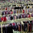 Stock Video: One womwatch goods among lot of clothes in shop