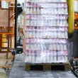 Stock Video: Automatic wrapper wraps stretch film bottles of yogurt on pallet