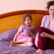 Mother and daughter sit on bed and watch tv with remote control — Stock Video
