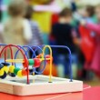 Stock Video: Close-up conundrum toy standing on table, in defocus behind it children play
