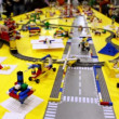 Stock Video: Kid play with toy railroad among different objects