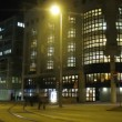 Stock Video: Trams and cars go on city in evening in front of library building