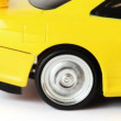 Rear wheel of yellow toy radio-controlled car slips on white background — Stock Video