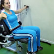 Stock Video: Young womsits and exercises on training equipment