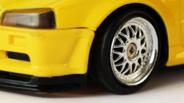 Front wheel of yellow toy radio-controlled car turns to right and left — Stock Video