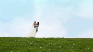 Newly-married couple runs to each other, embraces, then bride takes on hands of terrier — Stock Video