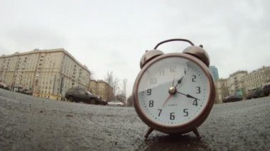 Clocks stands on roadside of road in front of moving cars — Stock Video