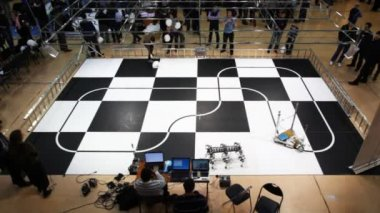 Robot toy car moves along line drawn on large chessboard — Stock Video