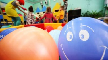 Inflatable ball is smiling, in defocus behind it children playing with clown and caregiver — Stock Video