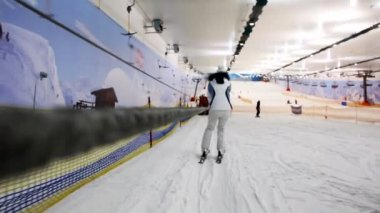 Girl in white dress goes down to ski on slope holding rope — Stock Video