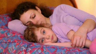 Madre con hija Acuestate en la cama, mamá duerme pero chica hace muecas — Vídeo de Stock
