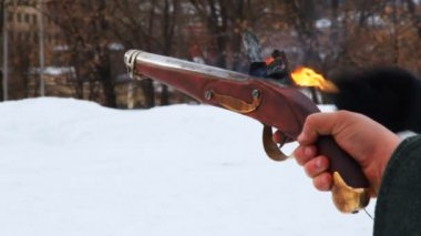 Hand of one man holds ancient pistol, and other lights fuse — Stock Video