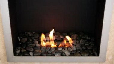 Tongues of flame go through slot in metal plate with stones around it in square fireplace — Stock Video