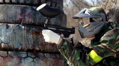 Ragazzo sit in agguato dietro pneumatici con paintball pistola e spara — Video Stock