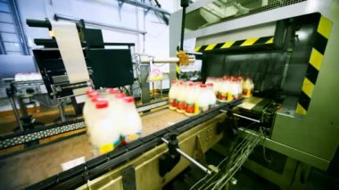 Packets bottles of milk go belt conveyor and automation pastes to back side sticker — Stock Video