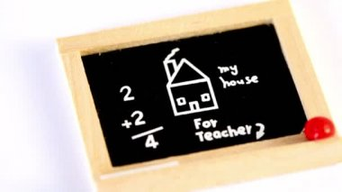 Small toy blackboard spins with drawing, inscription and computation — Stock Video