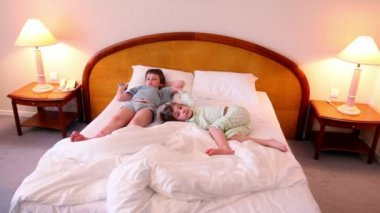Two kids boy and girl lay on bed in different poses and watch tv — Stock Video