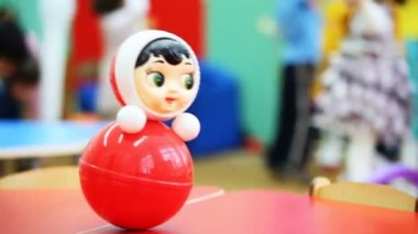 Roly-poly toy wobbles on table, in defocus behind it children play — Stock Video