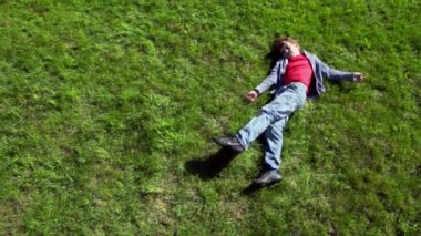 Little boy lay on grass plot and then rolls away — Vídeo Stock