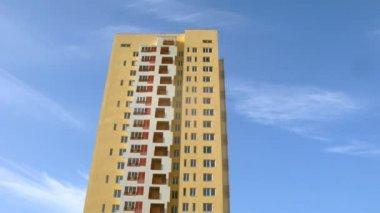 Grattacielo di colore giallo si leva in piedi contro il cielo blu — Video Stock