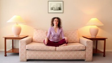 Woman sits on sofa in lotos pose, then closes her eyes and meditates — Stock Video