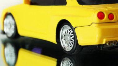 Wheels of yellow toy radio-controlled car rotate back and forth on mirror surface — Stock Video