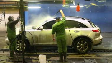 Dwóch pracowników umyć samochód wewnątrz silne strumienie wody — Wideo stockowe