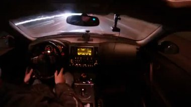 Man drives in car salon on high-speed highway at night — Stock Video #30656481