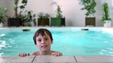 Little boy swims in basin pushes off from pool edge — Stock Video