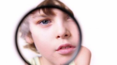 Little boy moves magnifying glass in front of his face and enlarge it — Stock Video