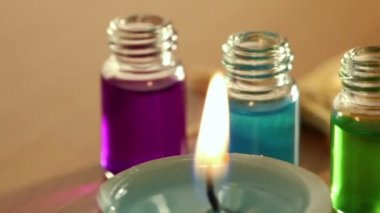 Two candles burn, few open bottles with color aroma oil and sea star lay — Stock Video