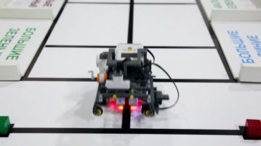Small robot moves and take green cub — Stock Video