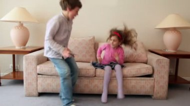 Two kids boy with girl come in room, sit and jump on sofa — Stock Video