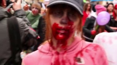 Girl wearing cap walk with blood on face and black eyes during Zombie Parade — Stock Video
