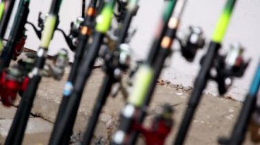 Lot of fishing rods stand near wall — Stock Video