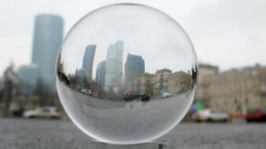 Business center Moscow City is visible through transparent glass ball lying on road — Stock Video